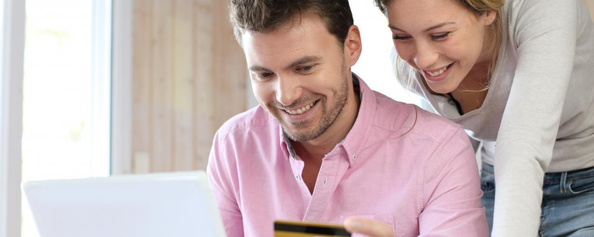 Happy man and woman with a credit card in front of a laptop