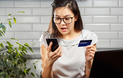 Fear and frustration - woman with a credit card and phone