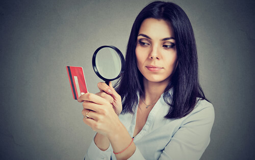 Woman looking through a magnifying glass at a credit card