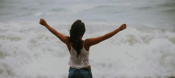 Woman with stretched arms in front of the ocean
