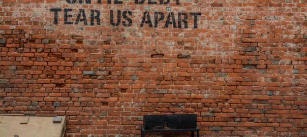"Wall that has writing ""Until Debt Tear Us Apart"""
