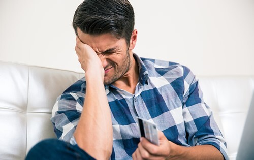Man holding a credit card and stressed