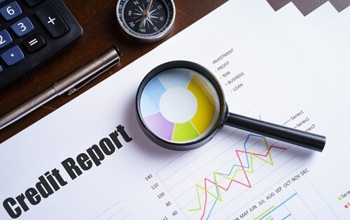 Study a credit report with a magnifying glass
