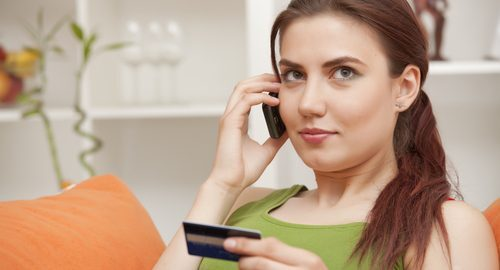 Young woman on the phone and holding a credit card